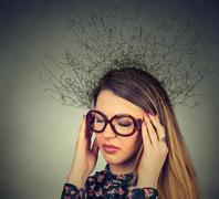 Closeup sad young woman with worried stressed face expression and brain melti Stock Photos