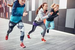 Three female runners racing up from underpass - stock photo