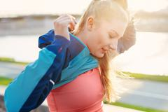 Mid adult female runner removing tracksuit top at city riverside - stock photo