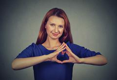 Smiling cheerful happy young woman making heart sign with hands Stock Photos