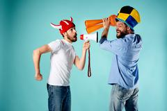 The two football fans with mouthpiece over blue Stock Photos