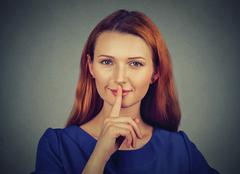 Secretive young woman placing finger on lips asking shh, quiet, silence Stock Photos
