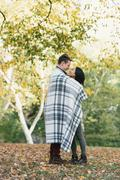 Romantic mid adult couple wrapped in blanket in park - stock photo