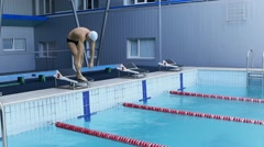 Professional swimmer makes the jump into the pool - stock footage