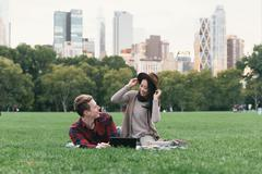 Mid adult woman trying on felt hat for boyfriend in Central Park, New York, USA Stock Photos