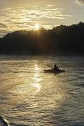 Silhouetted kayaker on Wimbleball lake at sunrise, Exmoor, Somerset, England - stock photo