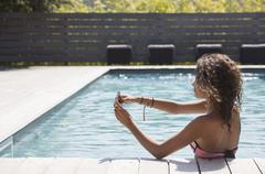 Girl in swimming pool taking smartphone selfie, Cassis, Provence, France - stock photo