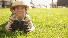 Child wearing pith helmet is playing in summer day with binoculars lying down Stock Footage