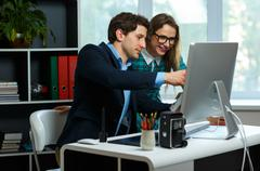 Young colleague - man and woman working from home - modern business concept - stock photo