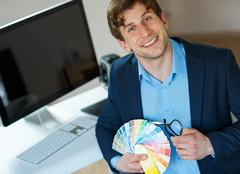 Young man looking to a color paint palette - stock photo