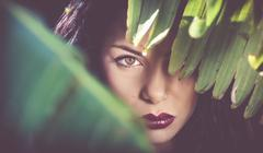 Portrait of beautiful sultry young woman behind leaves at night - stock photo