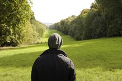 Rear view of man looking out at landscape, Great Missenden, Buckinghamshire, U.K - stock photo