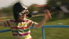 Child wearing aviator glasses is playing in summer day on carousel Stock Footage