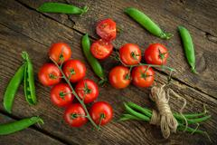 Fresh tomatoes with asparagus and green peas on a wooden background - stock photo
