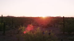 Slow Motion Shot of Desert Hikers at Sunset with Lens Flares Stock Footage