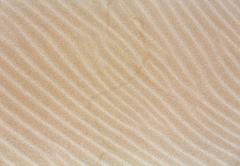Sand background with barely visible waves. Stock Photos
