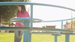 Asian child is playing in summer day on carousel in town park Stock Footage