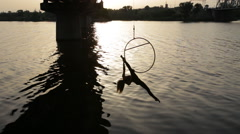 Woman doing show acrobatic trick on aerial hoop above the water - stock footage