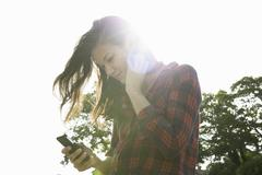 Young woman reading smartphone texts against sunlit sky Stock Photos