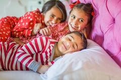 Cute boy and two sisters lying in bed giggling Stock Photos