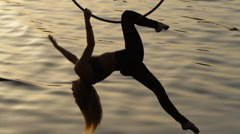 Woman doing show acrobatic trick above the water - stock footage