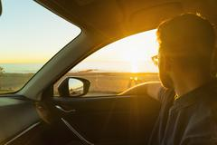 Young man looking out of car window at sunset - stock photo