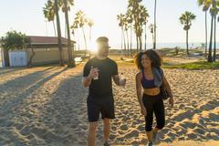 Couple wearing sports clothing, walking along beach, talking - stock photo