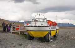 Excursion with a boat on wheels in orange lifejackets, The Jokulsarlon is the Stock Photos