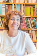 Portrait of mature female senior student in front of bookshelf Stock Photos