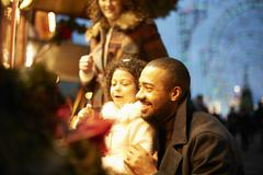 Young family at funfair at night, having fun Stock Photos