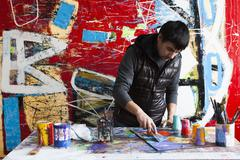 Male artist creating painted artwork - stock photo