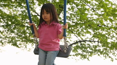 Asian girl child enjoy plays in summer day on swing at town park Stock Footage