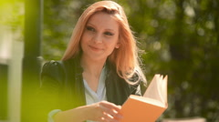 Young beautiful blonde girl in summer day is reading a book sit Stock Footage
