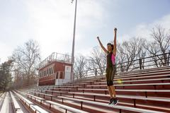 Young woman wearing sports clothing, arms raised, celebrating - stock photo