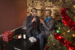 Male couple celebrating Christmas, holding wine glasses, making a toast - stock photo