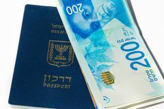 Stack of israeli money bills of 200 shekel and israeli passport - Top view Stock Photos