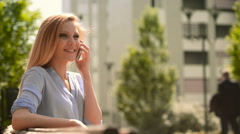 Young beautiful blonde girl on the smartphone sit on a bech Stock Footage