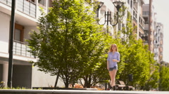 Young beautiful blonde girl walks at urban city park street listening music - stock footage