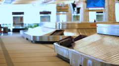 Travelers waiting for their luggage at the baggage carousel. Stock Footage