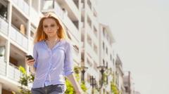 Young beautiful blonde girl walks at urban city park street listening music Stock Footage