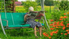 Old women with the newspaper is sitting on the swing in the garden - stock footage