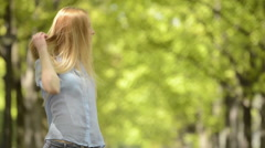 Young beautiful blonde girl portrait in summer day at urban city park Stock Footage