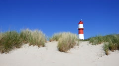 Dunes in front of a Lighthouse on frisian small holiday island Stock Footage