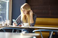 Young woman alone in cafe reading smartphone texts Stock Photos