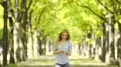 Young beautiful blonde girl walks at urban city park listening music Stock Footage