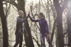 Couple in forest wearing sport clothing doing high five smiling Kuvituskuvat