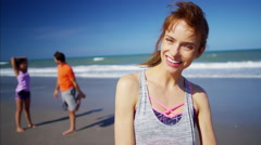 Portrait of Caucasian American female enjoying exercise on their beach holiday Stock Footage