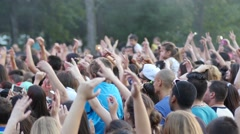 Cheering concert crowd people fans raising sway hands enjoying open air music - stock footage
