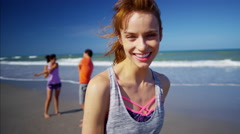 Portrait of Caucasian American sportswoman relaxing with friends on the beach Stock Footage