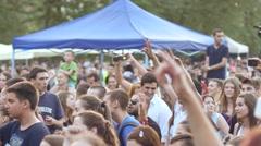 Pan camera of cheering big concert crowd people fans spectators enjoying music - stock footage